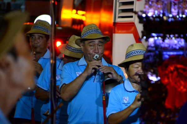 Participants of the night parade are playing their instruments.