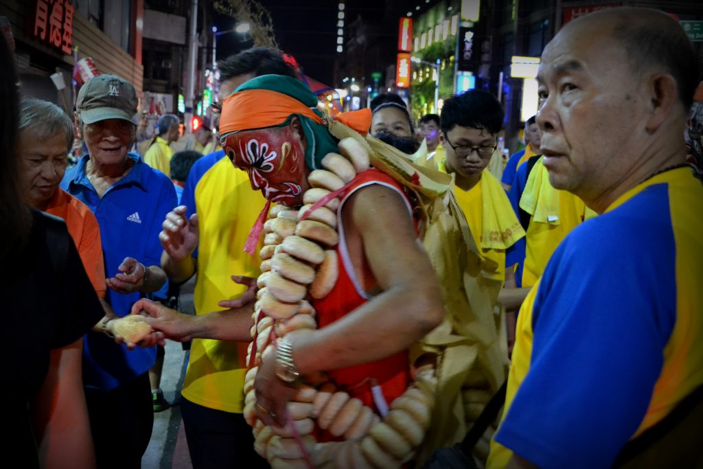 A participant of the night parade is giving bread to a visitor.