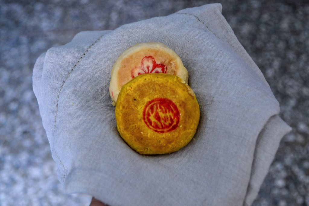 A person holding two moon cakes on a napkin