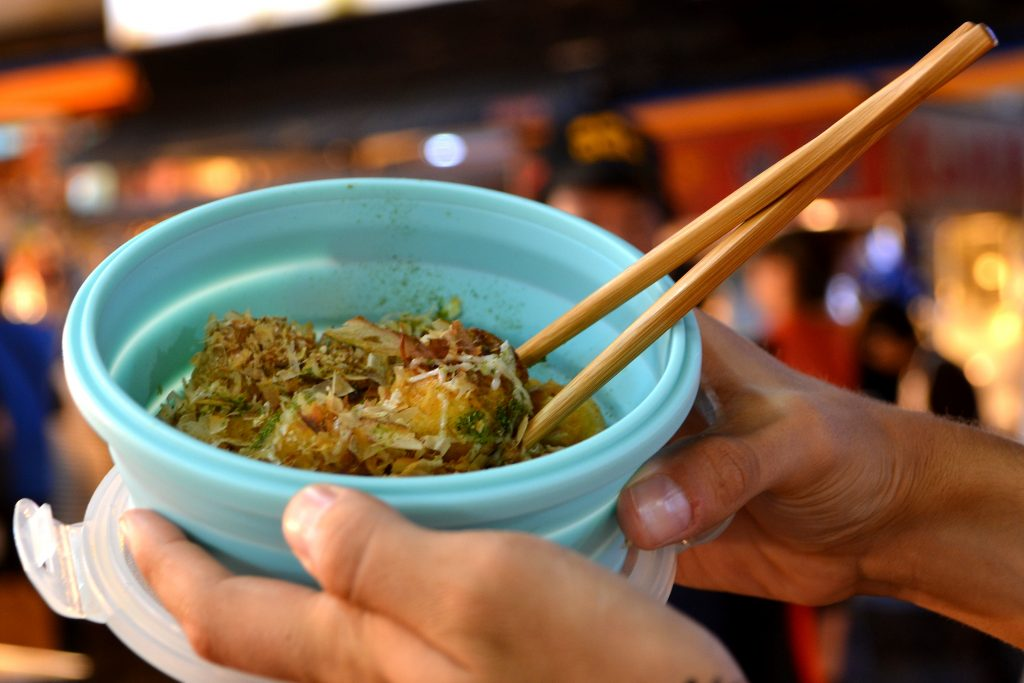 A person holding a dish from the night market in a reusable container in order to avoid plastic.